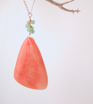 Large orange stone with green glass beads
